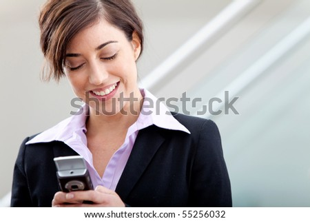 Business woman at the office texting from her cell phone