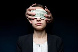 Business woman blinded by money. Dollars close her eyes and hands out of the darkness press money to her face