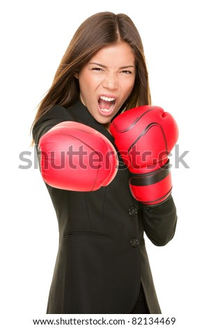 Business woman boxing punching towards camera ready to fight. Strength, power or competition concept image of beautiful strong Asian / Caucasian businesswoman isolated on white background.