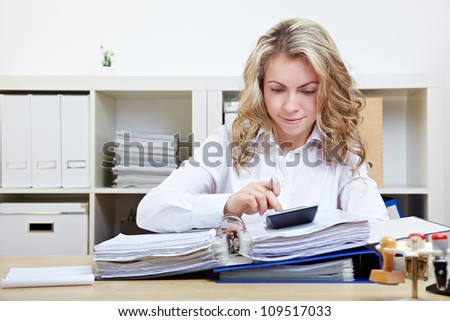 Business woman calculating invoice in her office at the desk