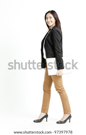 Business woman carrying laptop and walking on isolated white background