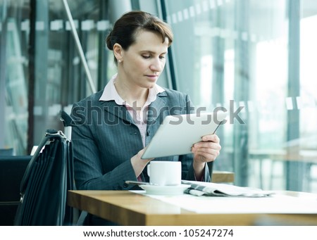 Business woman checking new on digital tablet at the airport business lounge