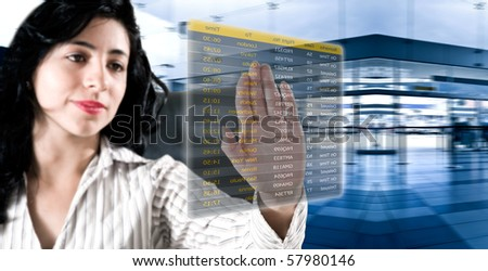 Business woman chosing her flight at the airport on a digital futuristic display
