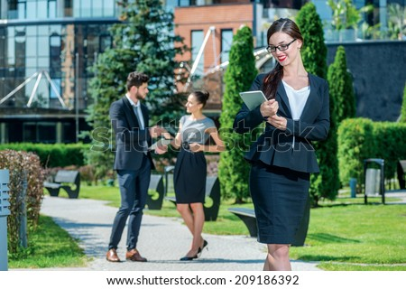 Business woman. Confident and successful woman holds a plate and stands outside the office and looks straight into the camera. On the background of businessmen are doing business
