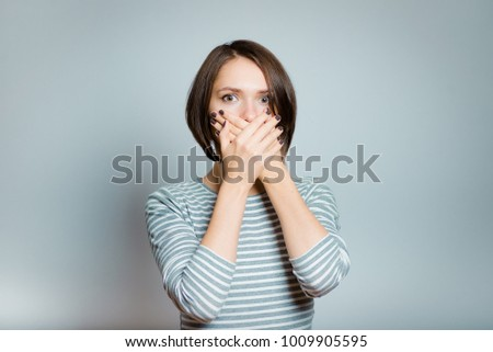 business woman covers her mouth with her hands, isolated on background, studio photo