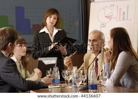 business woman demonstrating report to colleagues