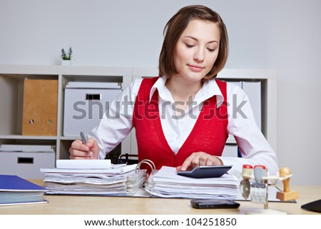 Business woman doing a tax audit in the office with files and calculator
