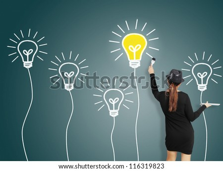 Business woman drawing light bulb - stock photo