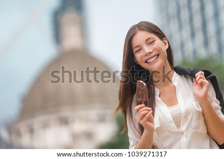 Business woman eating ice cream in Hong Kong. Young businesswoman enjoying ice-cream on at stick walking outside smiling happy in central Hong Kong. Mixed race Chinese Asian / Caucasian model on break