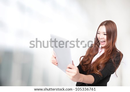 business woman excited looking at  Tablet pc (touch pad computer) at office. Cheerful happy fresh Asian female model. - stock photo