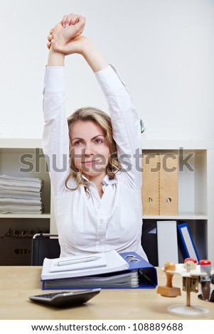 Business woman exercising her back in the office