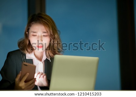 business woman feel tired use phone and notebook work at night #1210415203