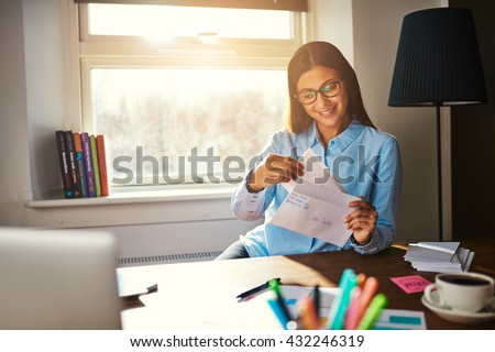 Business woman getting ready to mail a letter looking satisfied