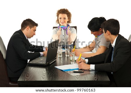 Business woman giving thumbs up at meeting while her colleagues working