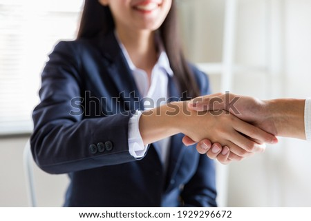 Business woman greeting with shake hands to congratulate after agreement with partner. Two business partners greeting together