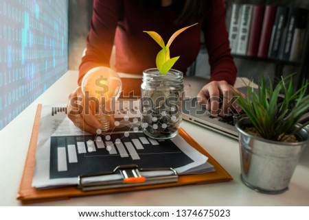 Business woman hand holding lightbulb with money stack and accounting finance in office, Finance And Investment Concept. #1374675023
