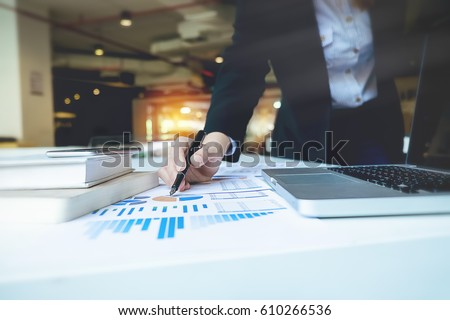 Business woman hand pointing  business document during discussion at meeting discussion and analysis data the charts and graphs showing the results at meeting.Business finances and accounting concept