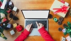 Business woman hand using laptop computer with blank white screen on wooden desk, christmas and happy new year online shopping concept