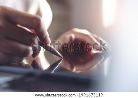 Business woman hand using stylus pen signing e document or digital release on digital tablet and working on laptop computer on office table, close up, paperless office, E-signing, Electronic signature Stock fotó ©