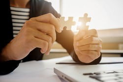 Business woman hands connecting jigsaw puzzle. Business solutions, success and strategy concept. Close up photo with selective focus.