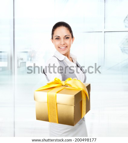 Business woman happy smile hold golden gift box in hands. Businesswoman in modern office