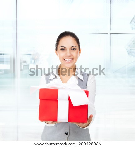 Business woman happy smile hold red gift box in hands. Businesswoman in modern office