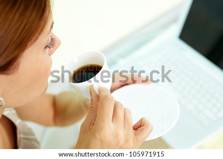 Business woman having a cup of coffee during the break