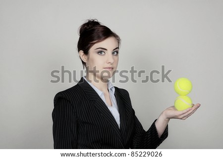 business woman hold out her arm with two tennis balls in her hand