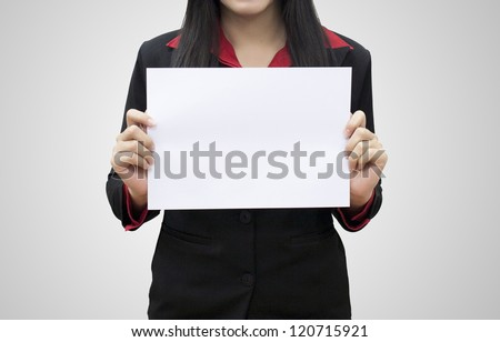 Business woman hold white blank paper. Young girl show blank board. Female model portrait isolated on grey background.