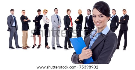Business woman holding a clipboard with her team behind - stock photo