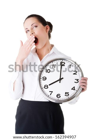 Business woman holding a clock and yeaning. Isolated on white.