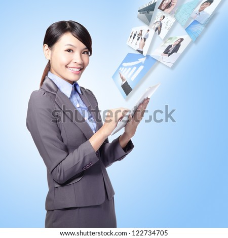 business woman holding a tablet pc and work with internet isolated on blue background, model is a asian girl