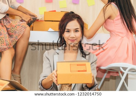 Business woman holding box and her friend working her business online at home office.