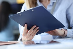 Business woman holding clipboard with documents in her hands at workplace. Management concept