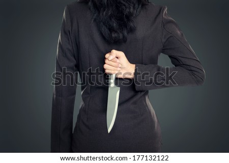 Business woman Holding Knife Behind Her Back. conceptual image