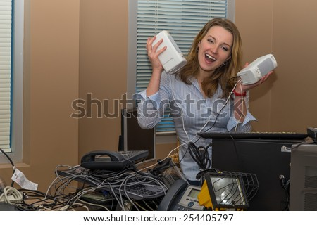 Business Woman holding  speakers in an office with many old phones in a mess