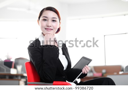 business woman holding tablet sitting on chair