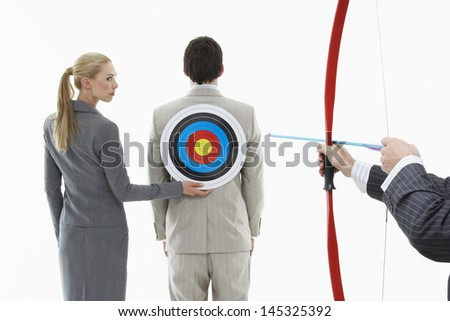 Business woman holding target to man's back while other man aims bow and arrow ストックフォト ©