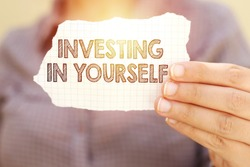 business woman holding tear paper with investing in yourself text