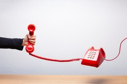 Business woman holding the red phone, urgent call waiting , classic red telephone receiver in hand wearing black suit, old telephone on white background, flying in weightlessness.