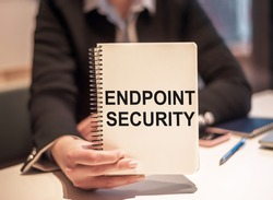 Business woman holds a notebook with the text Endpoint Security.