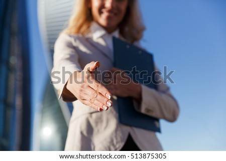Business woman holds out an open hand ready for handshake #513875305