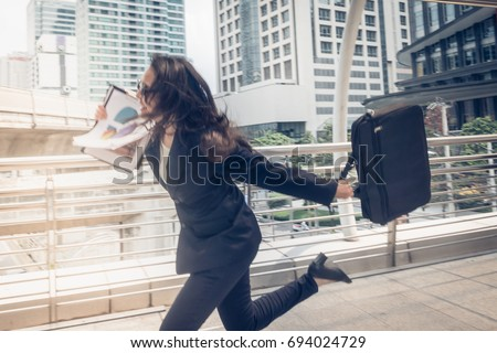 business woman hurry up and running in business city street for rush hour as motion blur