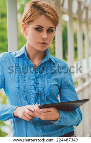 Business woman in a blue striped shirt with tablet pc leaning against the frame of the balcony