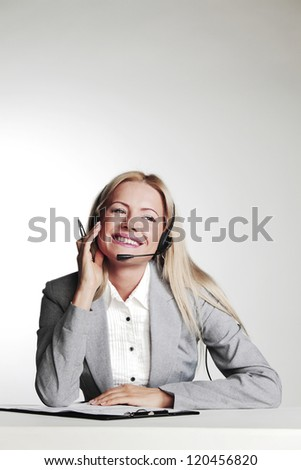 business woman in a headset writing in notebook