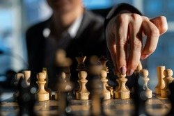 Business woman in a suit plays chess. Close-up of a female hand on a pawn