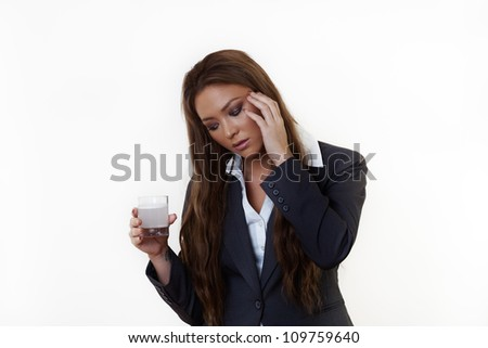 business woman in a suit with a bad headache drinking medicine hoping it will go away and make her feel better