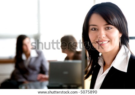 Business woman in an office with her team behind working on a laptop