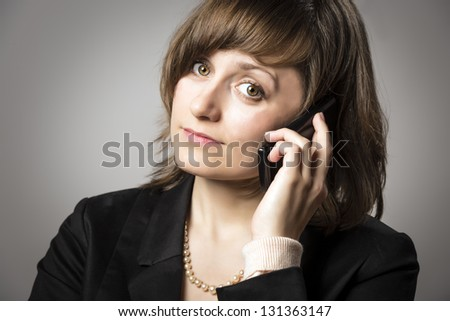 Business woman in black suit and pearls phone