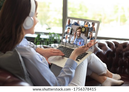 Business woman in headphones lying on sofa speak talk on video call with colleagues on online briefing during self isolation and quarantine. Webcam group conference with coworkers on laptop at office.